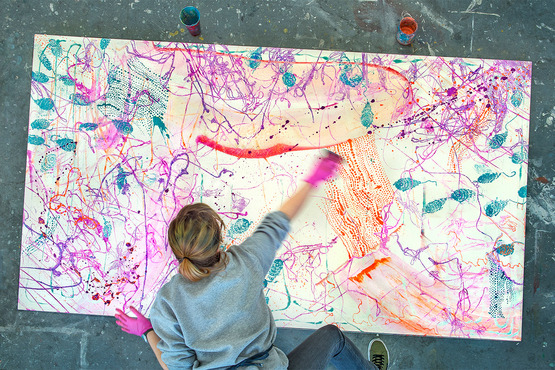 A student creating a large, abstract, colorful painting