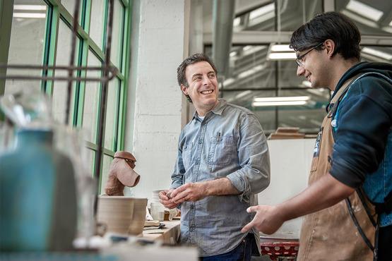 A professor talking to a student in the Ceramics studio
