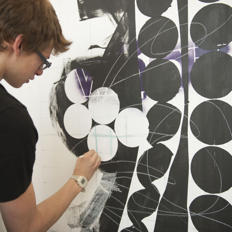 A student working on a large geometrical drawing