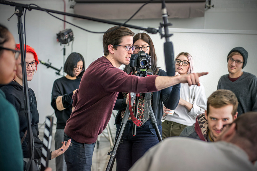 A professor directing a video shoot to a class