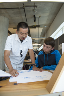 An instructor looks at a student's Industrial Design project.