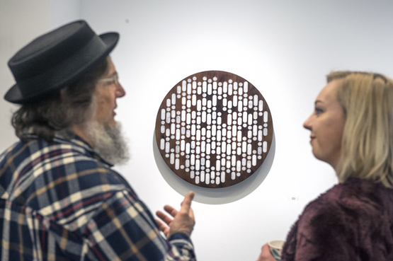 man and woman discussing wall sculpture