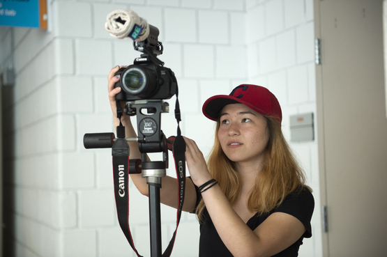 A student setting up a digital camera for a photo shoot.