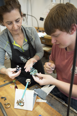 An instructor shows a student how to cast a metal piece from wax.