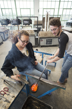 A current student helps a local teacher learn glassblowing.