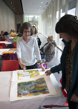 Teachers show off their prints after a printmaking workshop.