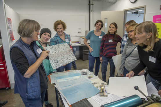 A group of teachers watching a printmaking demo.