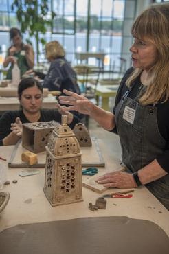 A teacher creating patterned slabs in a ceramics workshop.