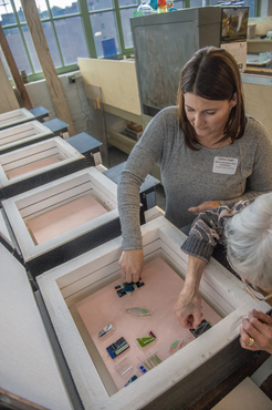 Teachers unload their glass pieces from a cooled kiln during a workshop.