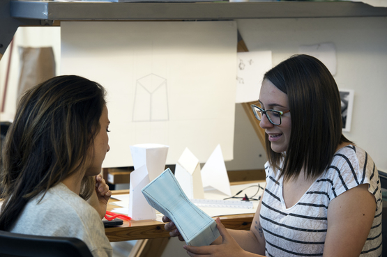A student shows their product design to their instructor.