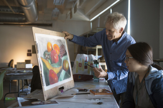 An instructor and student look at a pastel still life drawing.