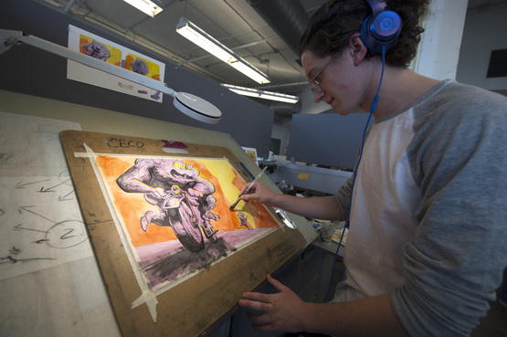 A student working on their illustration at one of the drafting tables.