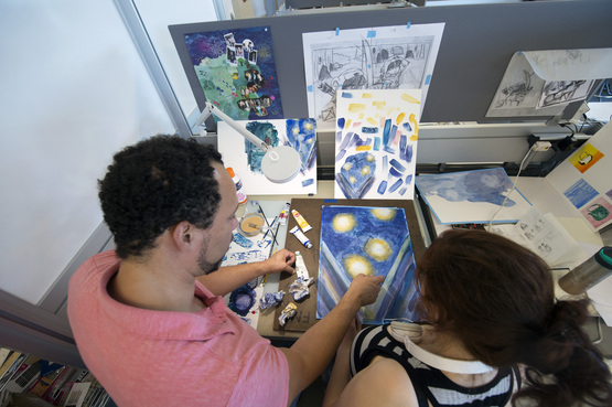 An instructor and student reviewing their work in an Illustration studio.