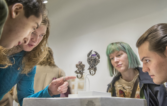 students discussing two pieces of metal/jewelry in exhibition