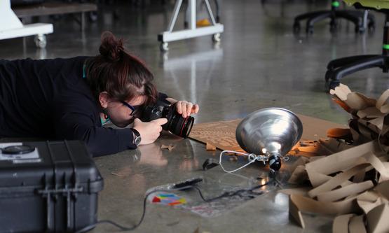 A teacher gets a close-up shot of a set up during an abstract photography workshop.