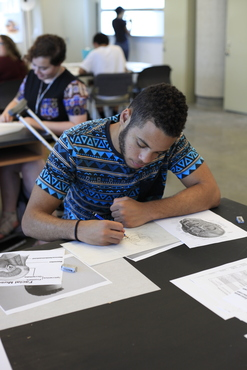 A student drawing with pencil in the Biomedical Art class.