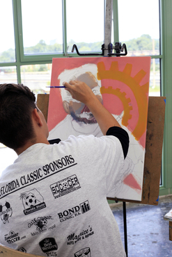 A student paints in the figure on their piece.