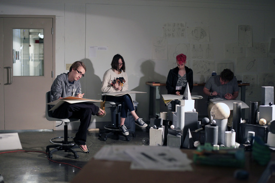 Students drawing a still life using dramatic lighting.