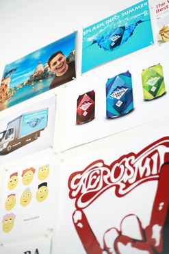 Various graphic design projects printed and hung on a wall.