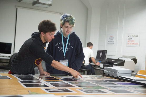 Students lay out various photos in the Photography course.