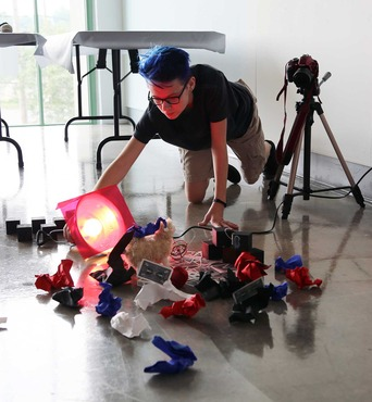 A student setting up dramatic lighting for a photography workshop.