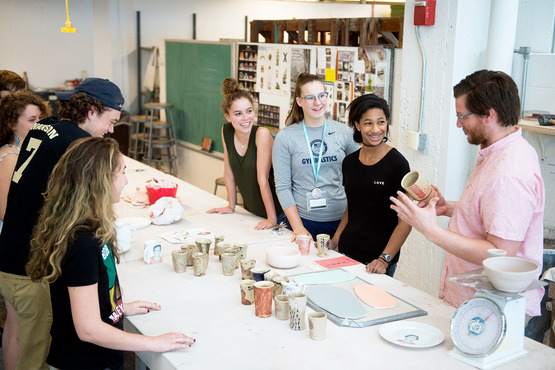 Students in the Print and Ceramics class gather around for a decal demo.