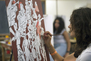 A student working on an abstract painting in class.